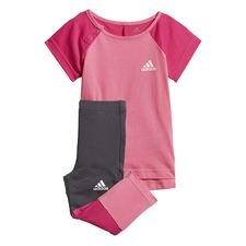 Et sæt i to dele til små atleter med store drømme. Dette babysæt har en kortærmet T-shirt og tilpassede tights. T-shirten har trykknapper på skulderen, så det e